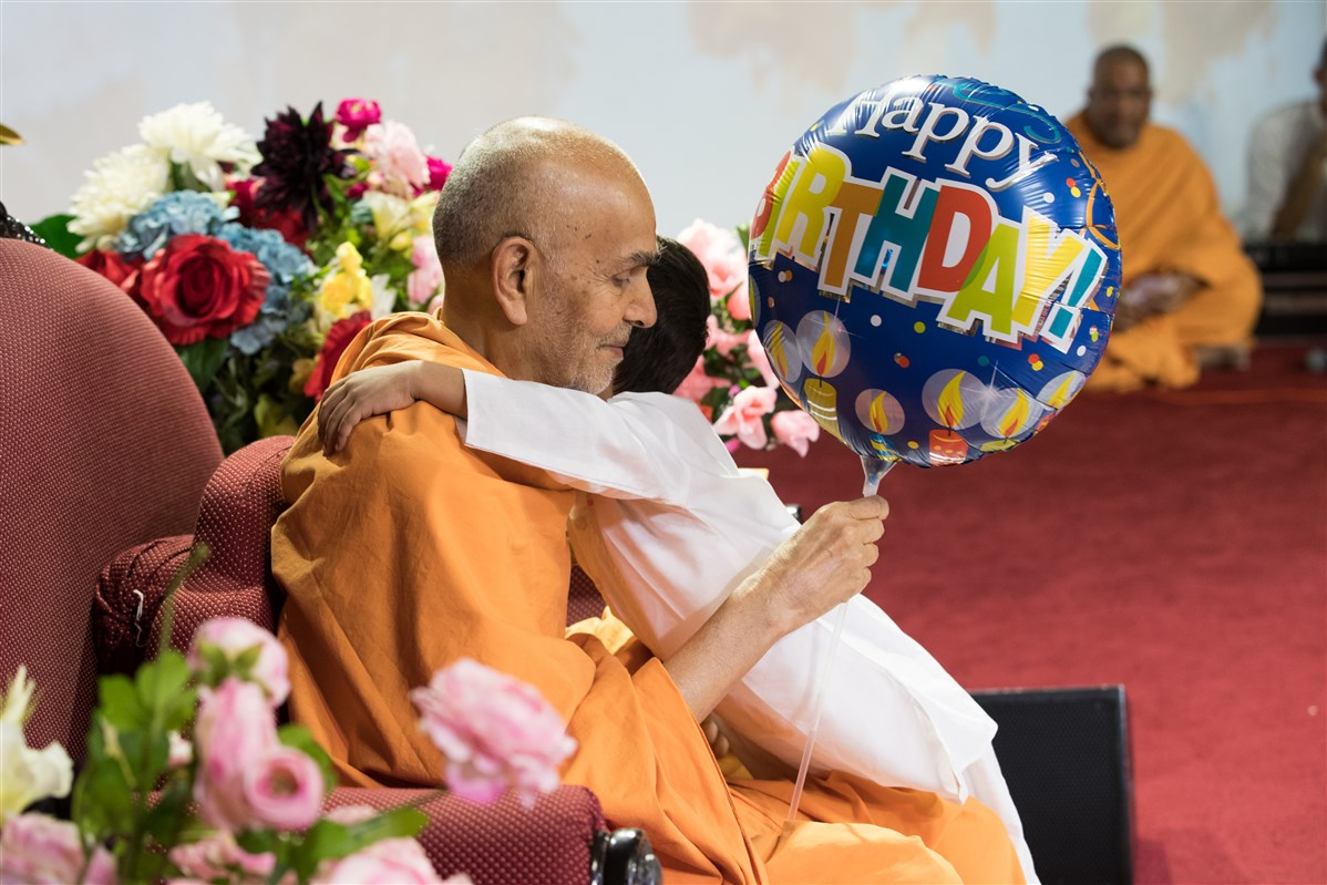 A child offers a balloon to Swamishri and hugs him