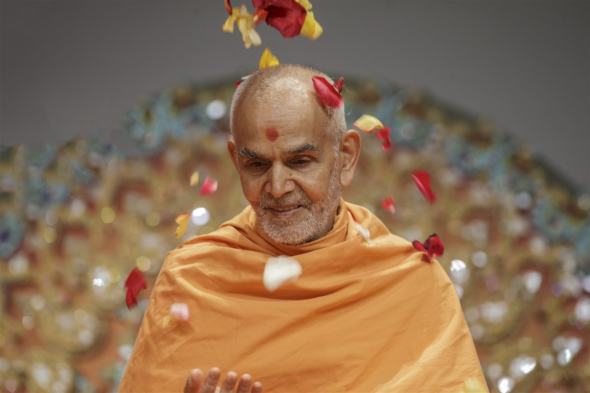 Swamishri is showered with flower petals
