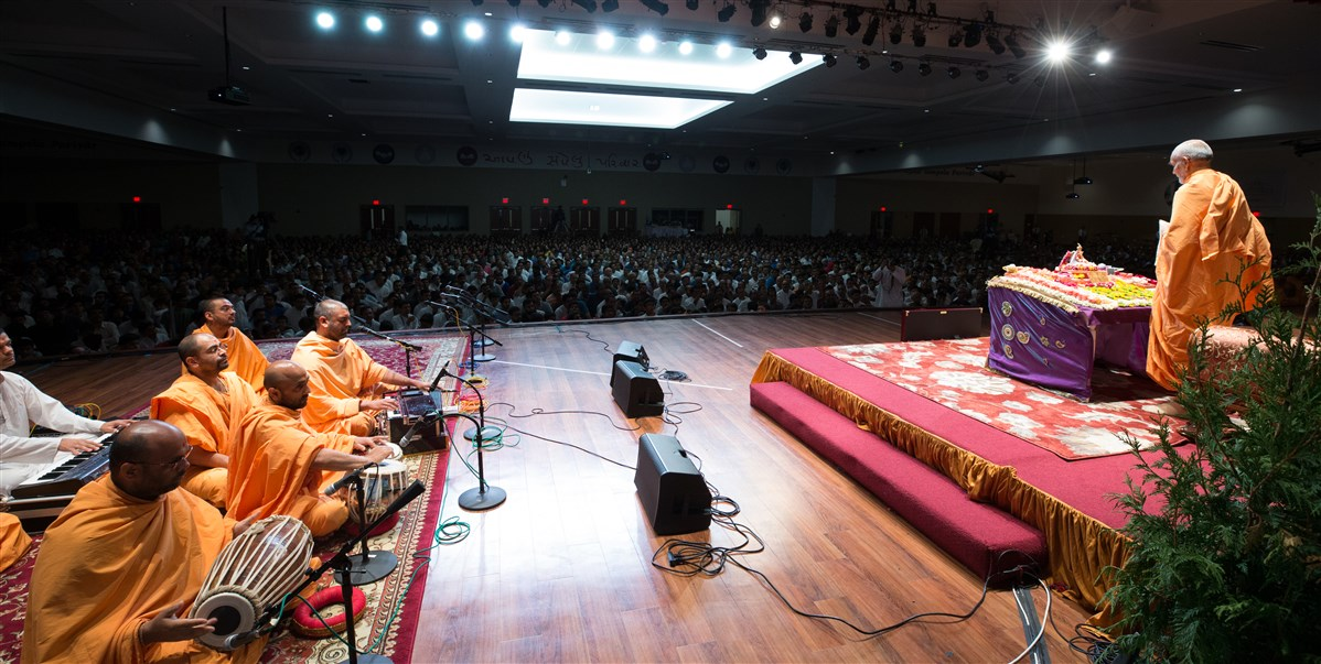 Swamis sing kirtans before Swamishri during puja