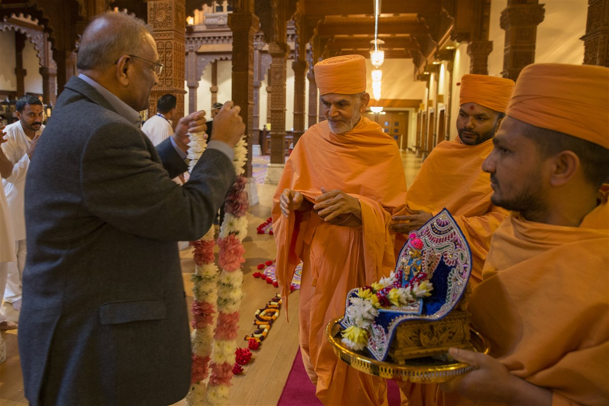 Param Pujya Mahant Swami Maharaj arrives with Shri Harikrishna Maharaj at BAPS Shri Swaminarayan Mandir, London and is greeted by a trustee