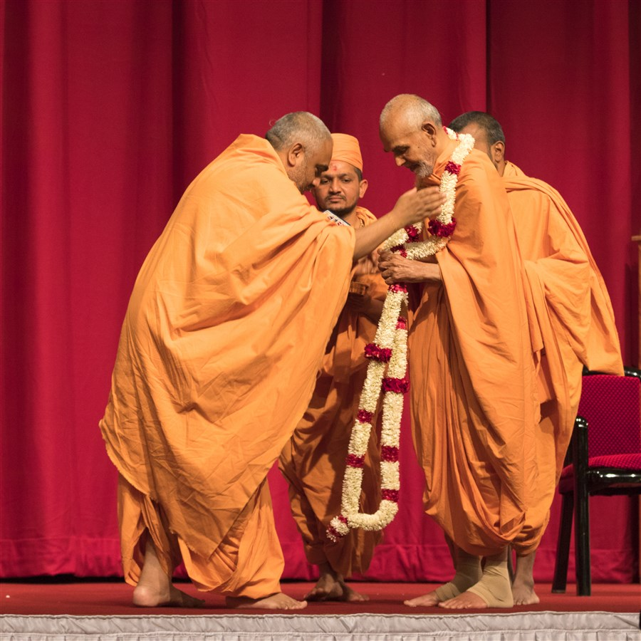 Yogvivekdas Swami honours Swamishri with a fresh flower garland on behalf of the UK & Europe Satsang fellowship