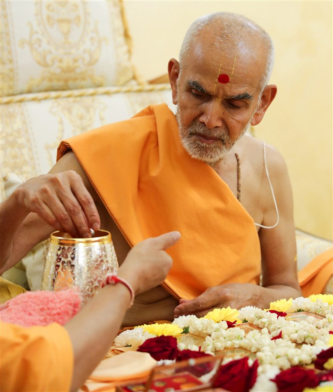 Swamishri sanctifies water with the prasadi items of Bhagwan Swaminarayan and the Guru Parampara