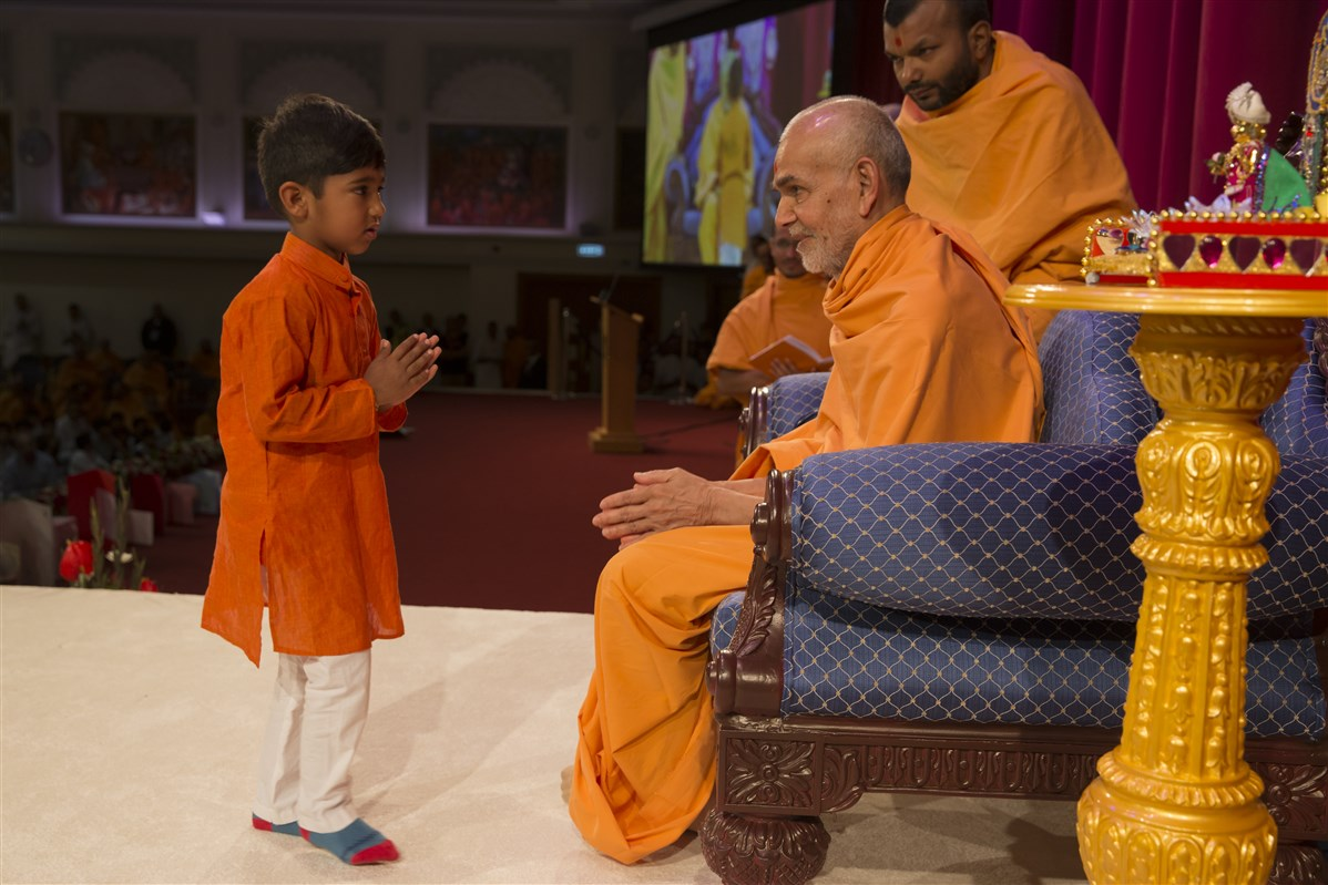 A child receives blessings after performing during Swamishri's puja