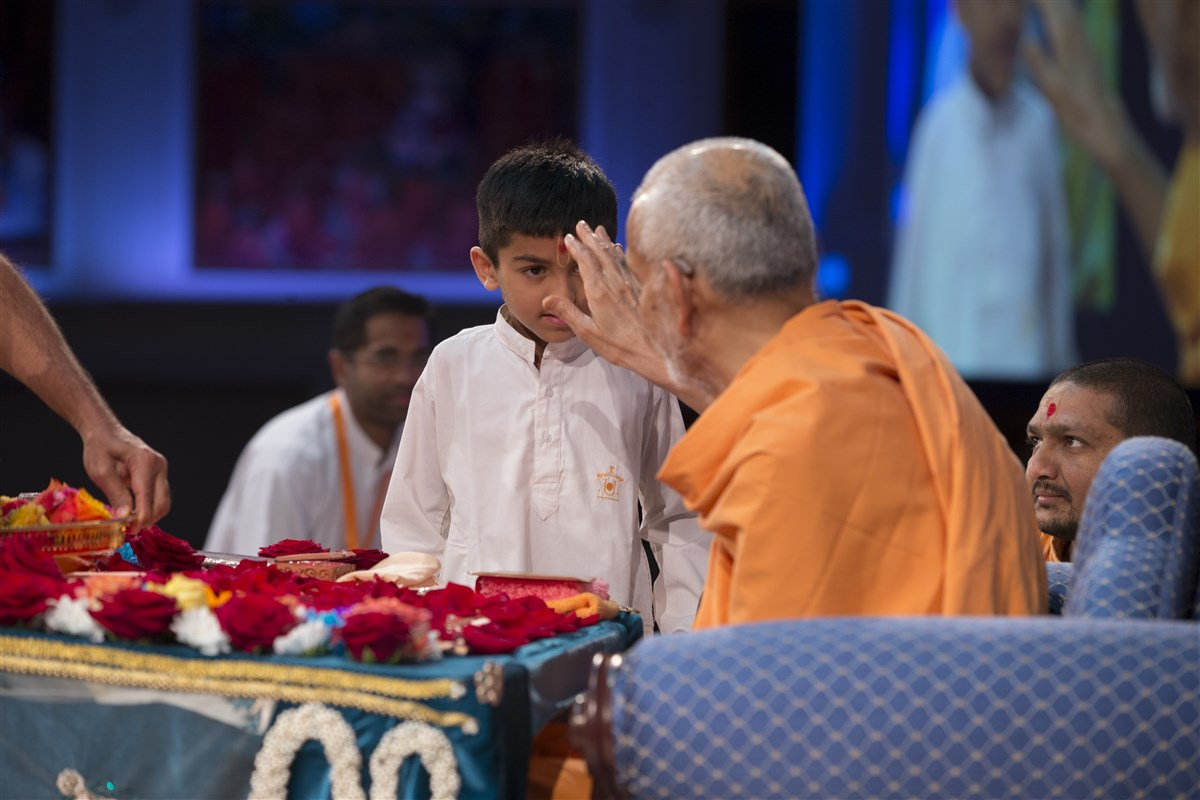 Swamishri blesses a child who recited scriptural quotations during the puja