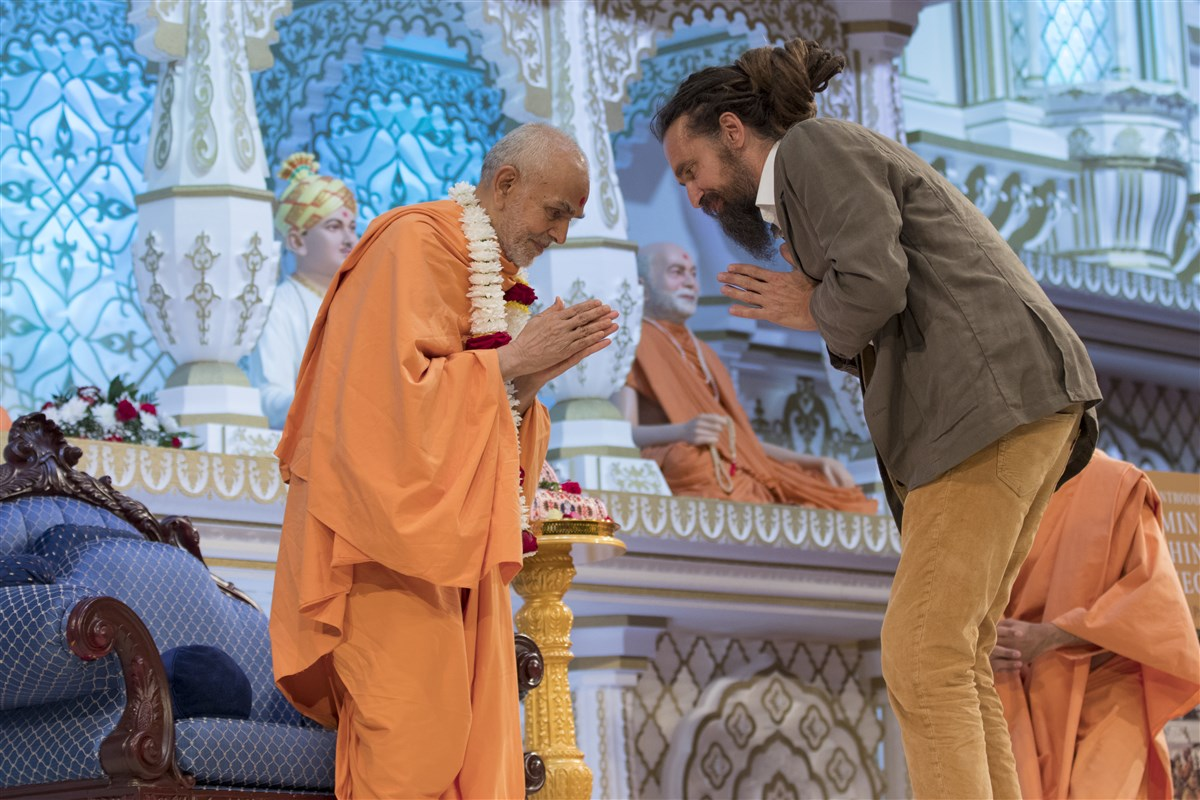 Dr Mallinson honours Swamishri with a garland and receives Swamishri's blessings