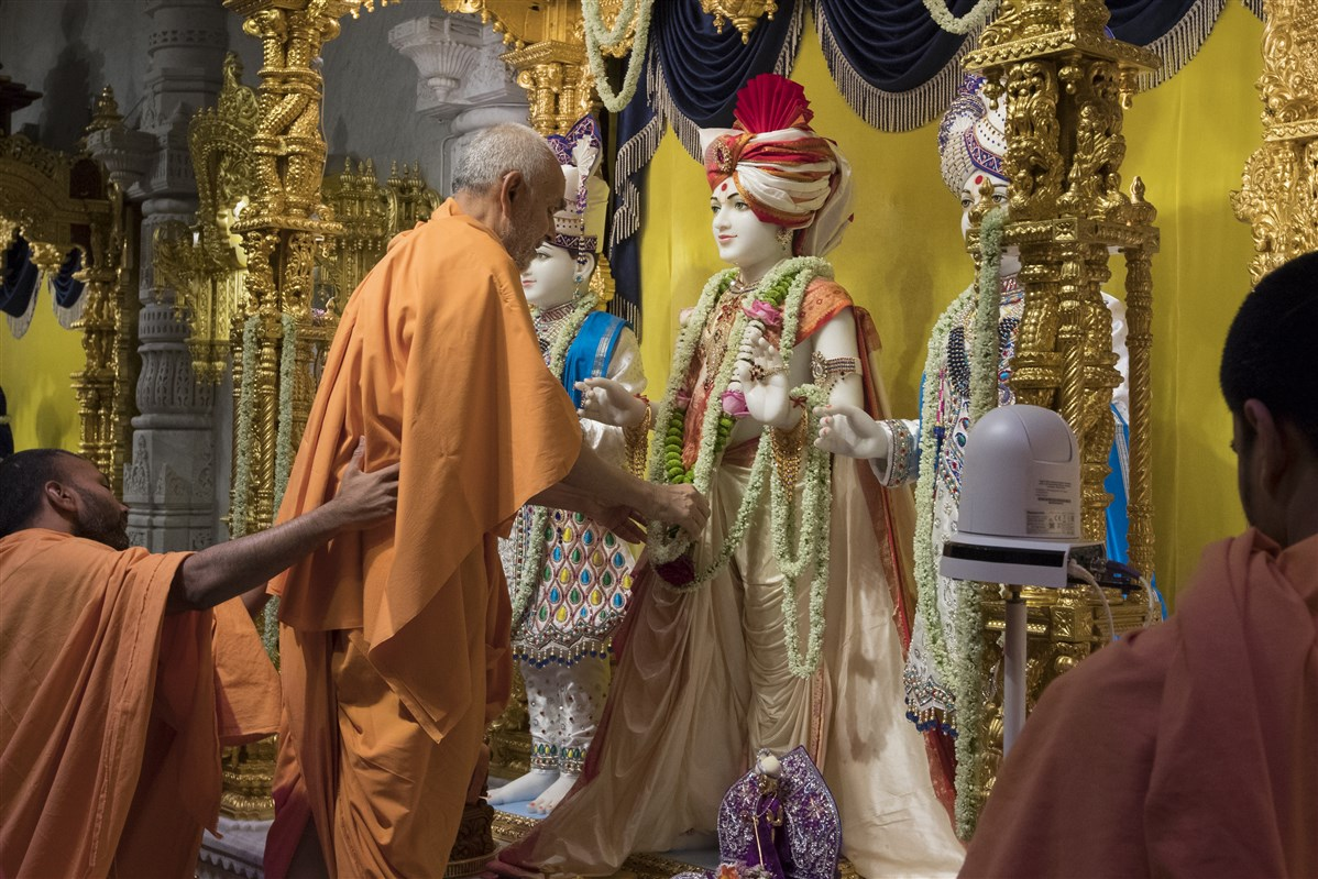 Swamishri adjusts the adornments of the murtis
