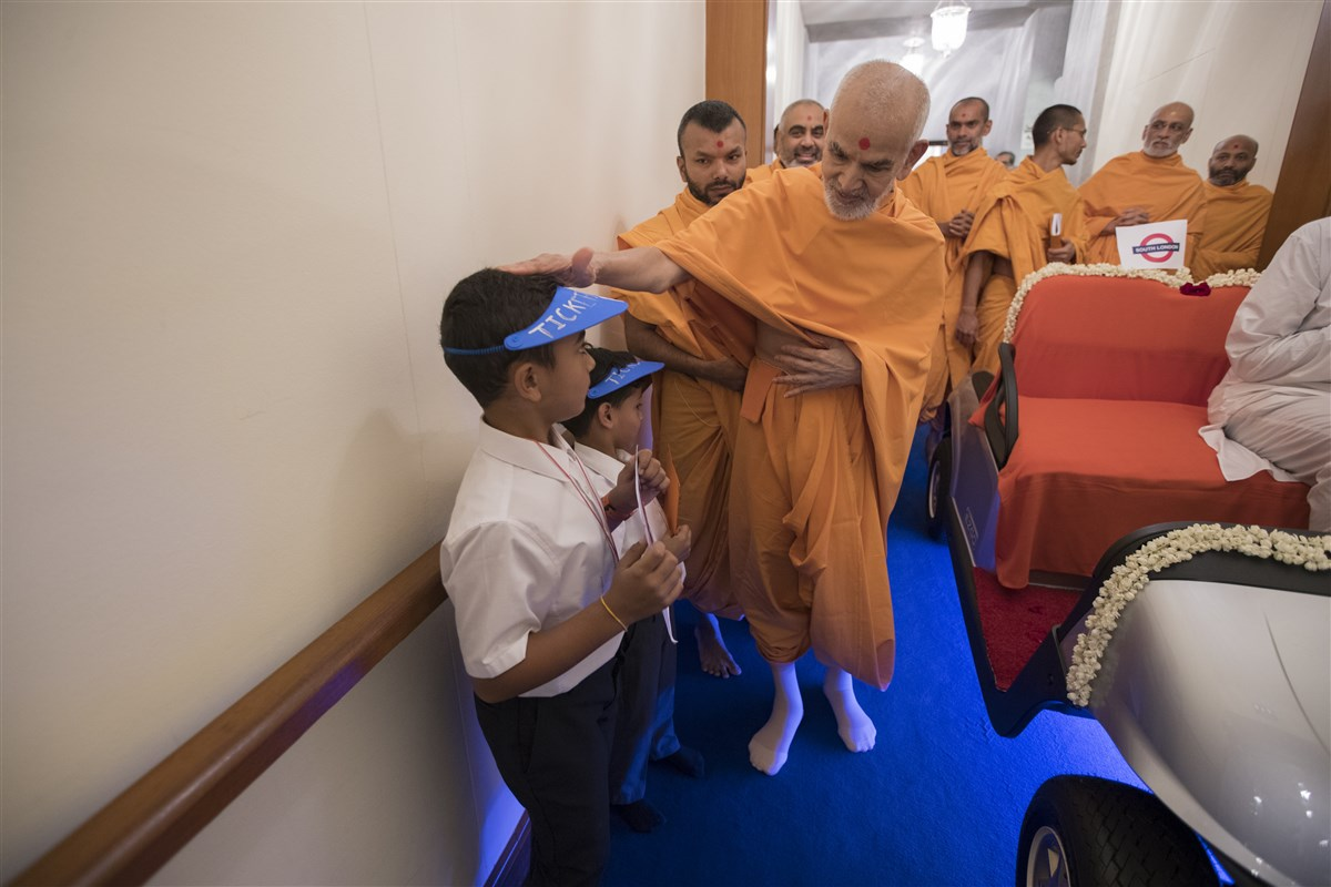 Swamishri blesses two children, posing as ticket masters