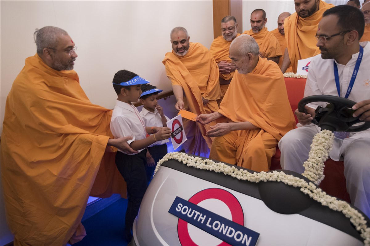 The 'ticket masters' present Swamishri with a ticket, from Neasden station to...