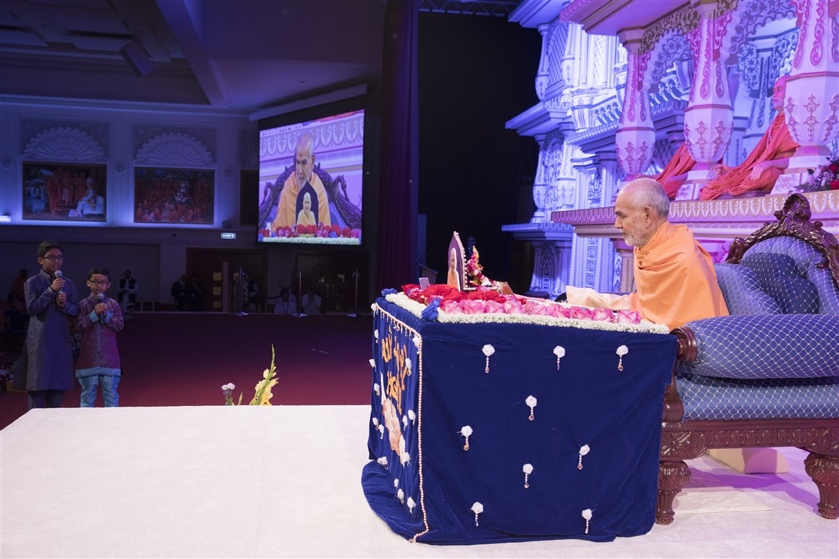 Children recite lofty excerpts from the scriptures during Swamishri's puja
