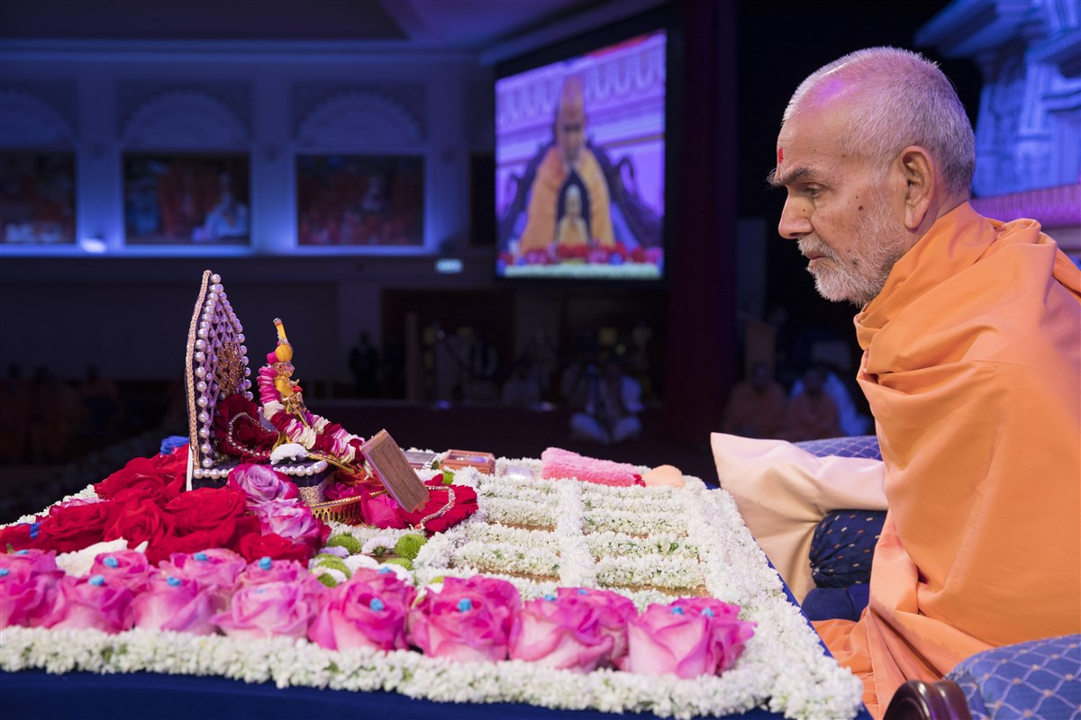 Swamishri engrossed in chanting the 'Swaminarayan' mahamantra with his mala