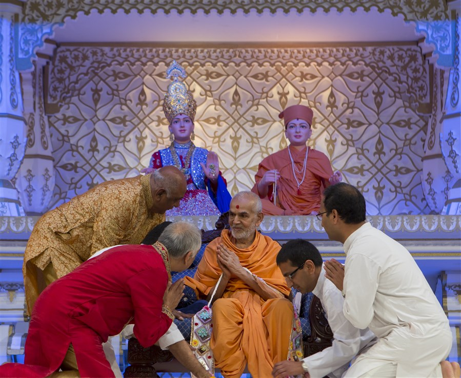 Lead volunteers of East London Satsang Mandal honour Swamishri with a decorative garland