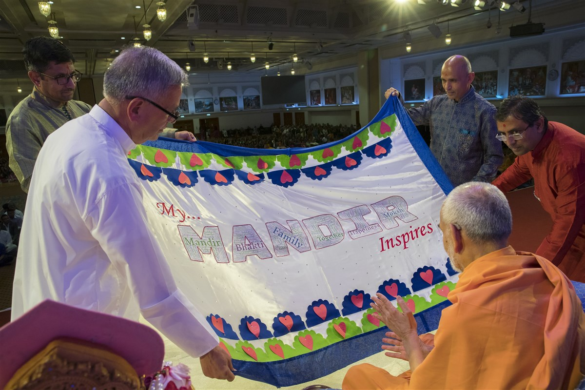 Devotees of East London present to Swamishri a decorative shawl with inspiring messages about their upcoming mandir
