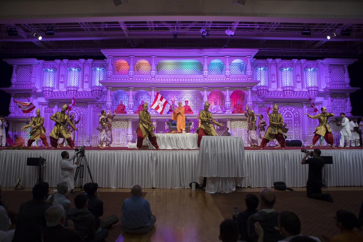 Children and youths of East London perform a dance before Swamishri