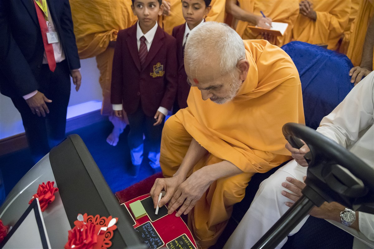 Swamishri inscribes an inspiring message for the pupils with a piece of chalk