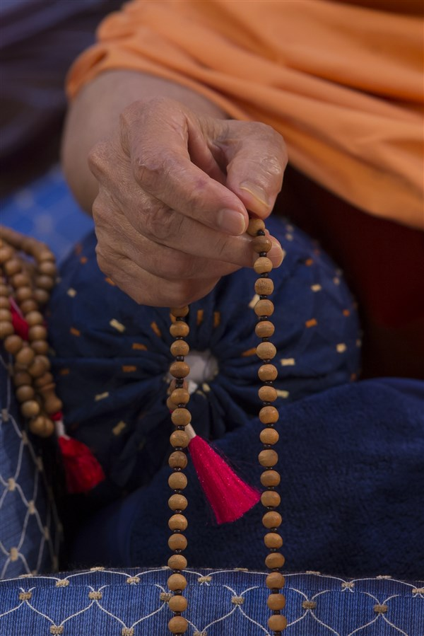 Swamishri rotates the mala as he listens to the presentations