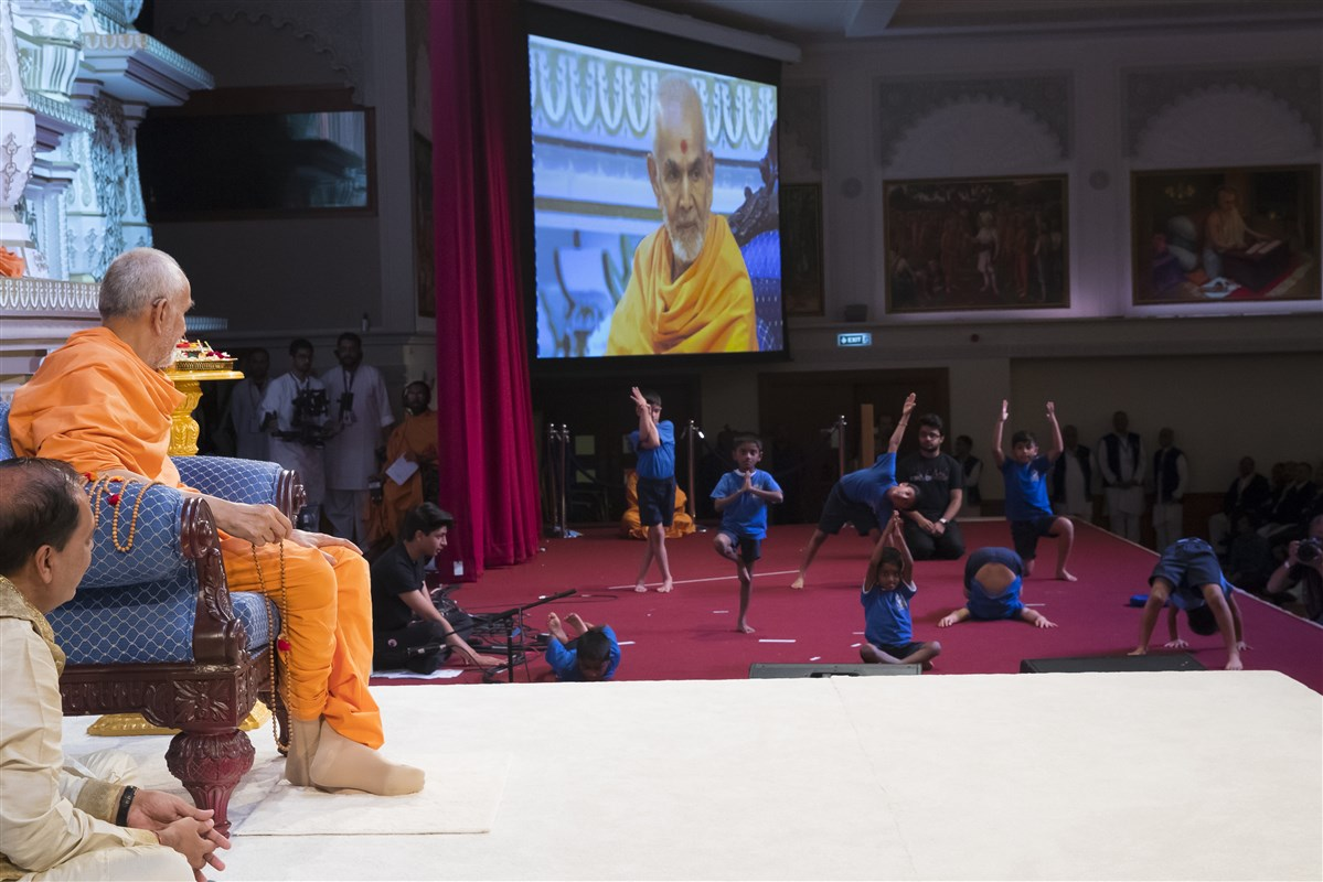 Young pupils perform yoga exercises before Swamishri