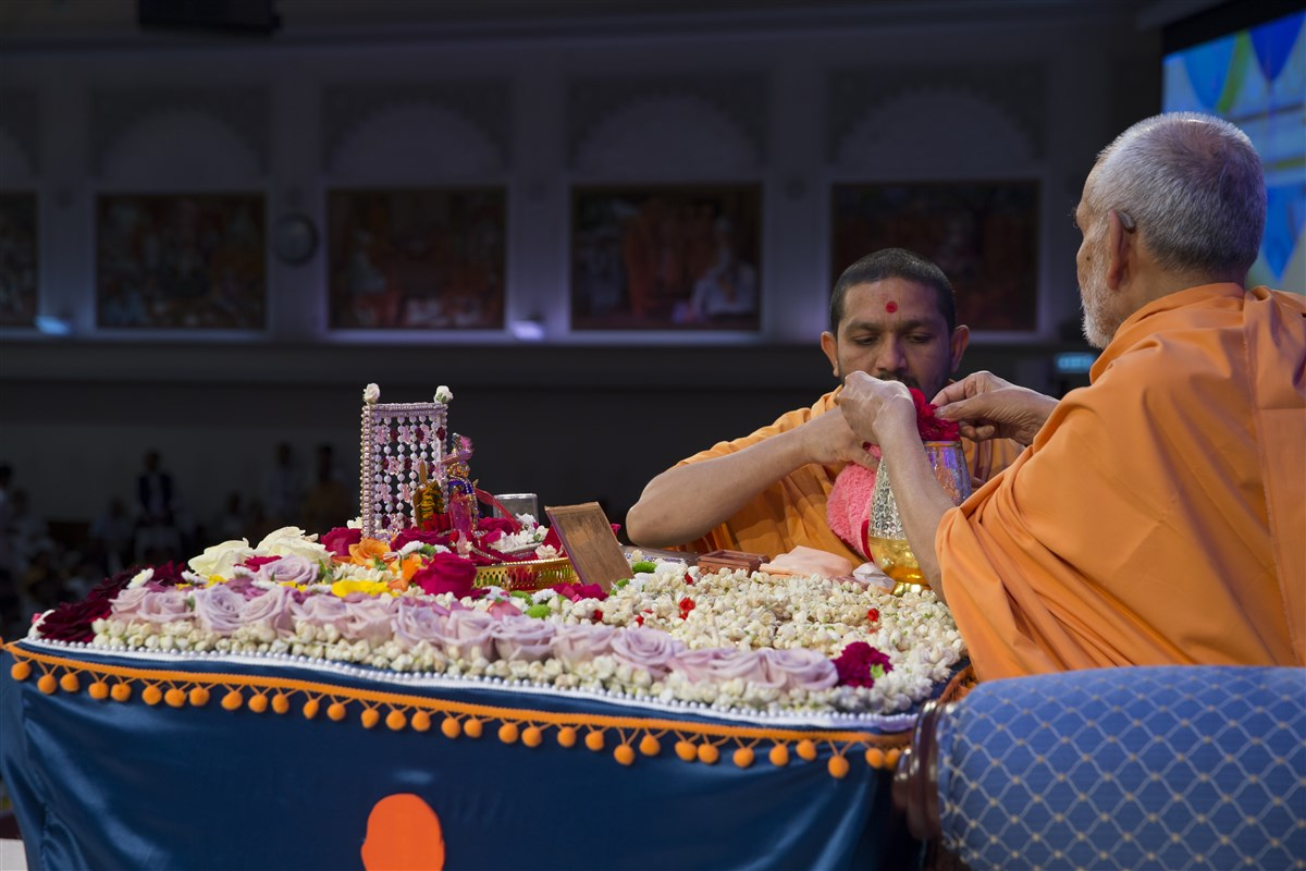 Swamishri sanctifies water with rose petals from his puja
