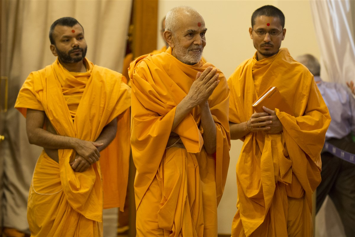 Param Pujya Mahant Swami Maharaj emerges from his room with folded hands
