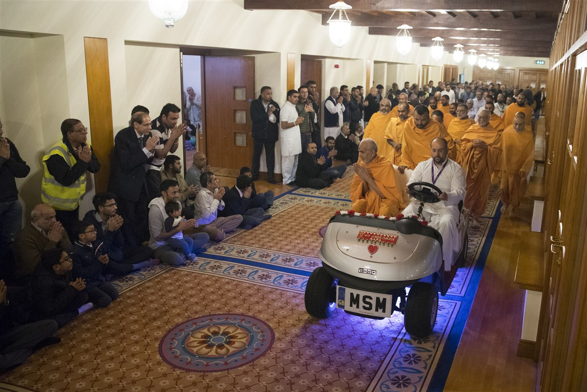 Swamishri proceeds to the assembly hall, greeting devotees with folded hands on his way