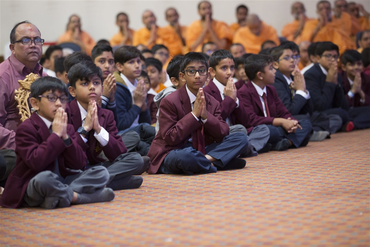 Pupils from The Swaminarayan School greet Swamishri with folded hands