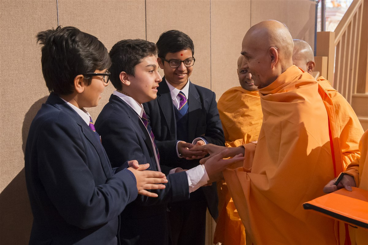 Swamishri engages with and blesses children as he departs the hall