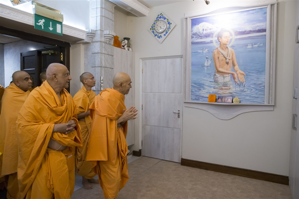 Swamishri bows with folded hands to a painting of Shri Nilkanth Varni