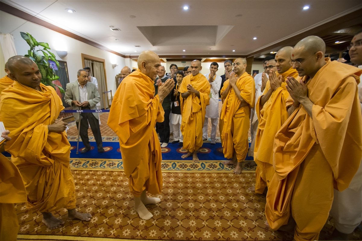 Param Pujya Mahant Swami Maharaj greets swamis with folded hands upon leaving his room