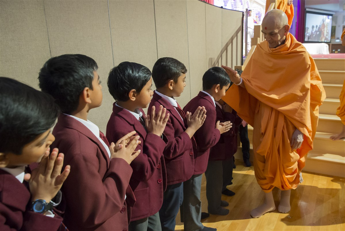 Swamishri blesses children as he departs from the assembly hall