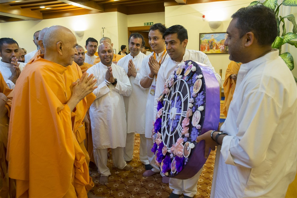 Volunteers present Swamishri with a floral clock