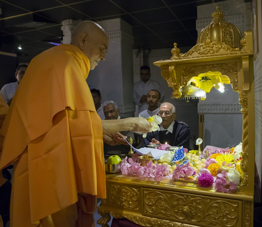 Swamishri offers flowers to the mahapuja