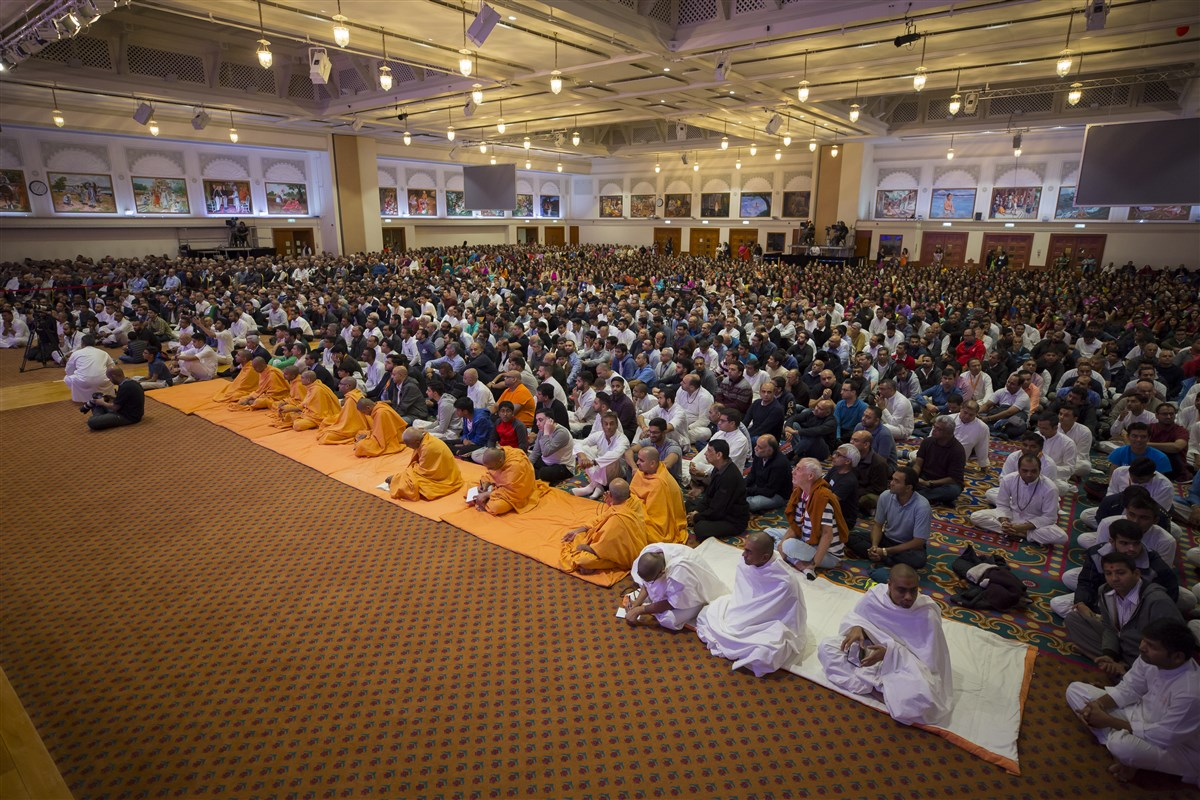 Devotees observe and participate in the guru pujan