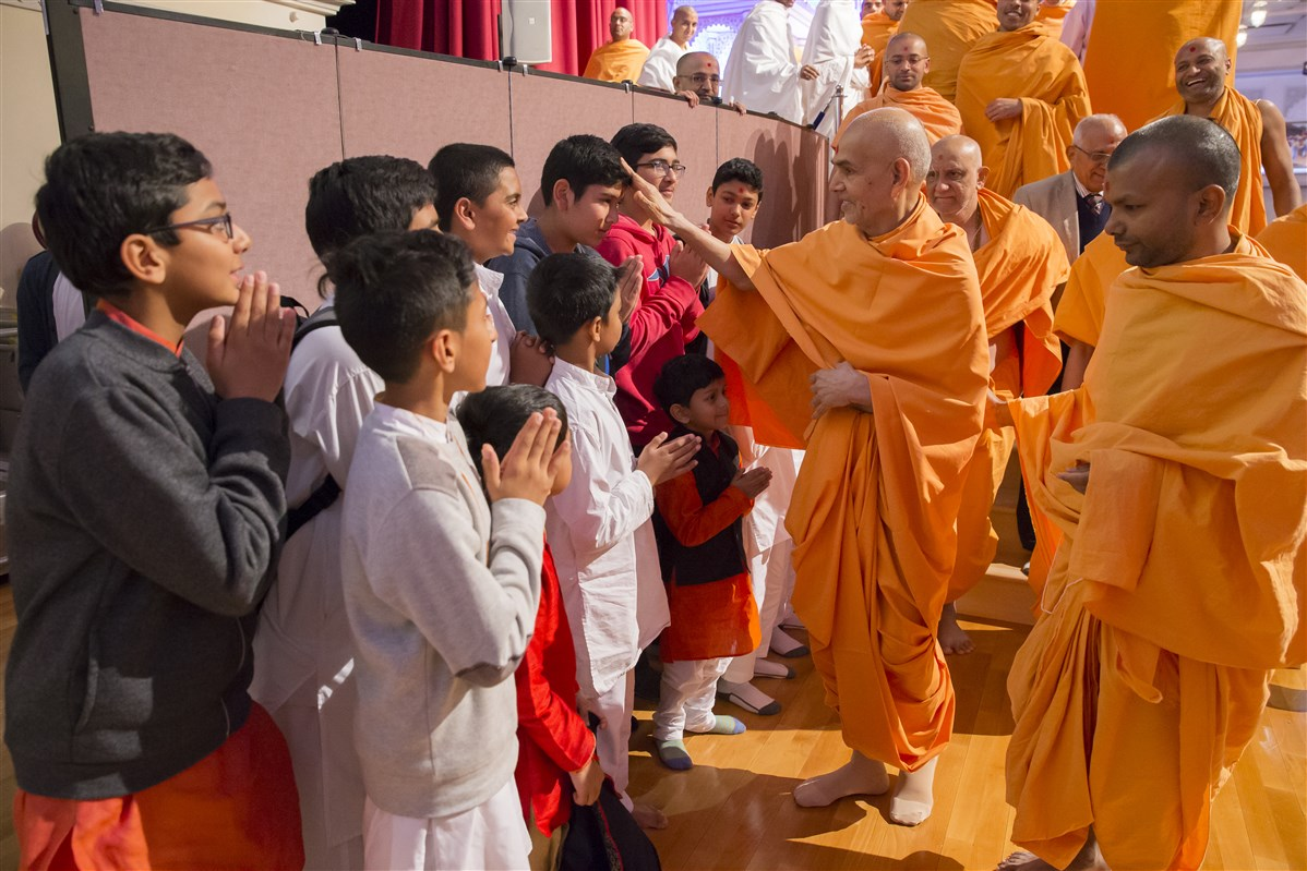 Swamishri blesses children as he departs the assembly hall