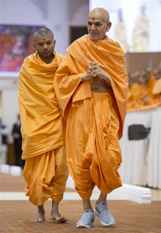 Swamishri performs his evening walk in the assembly hall, greeting devotees as he passes