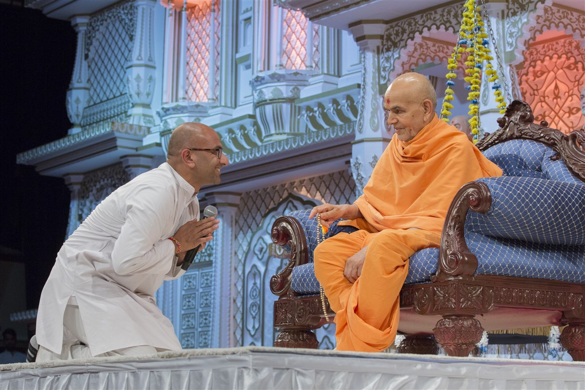 A husband prays before Swamishri