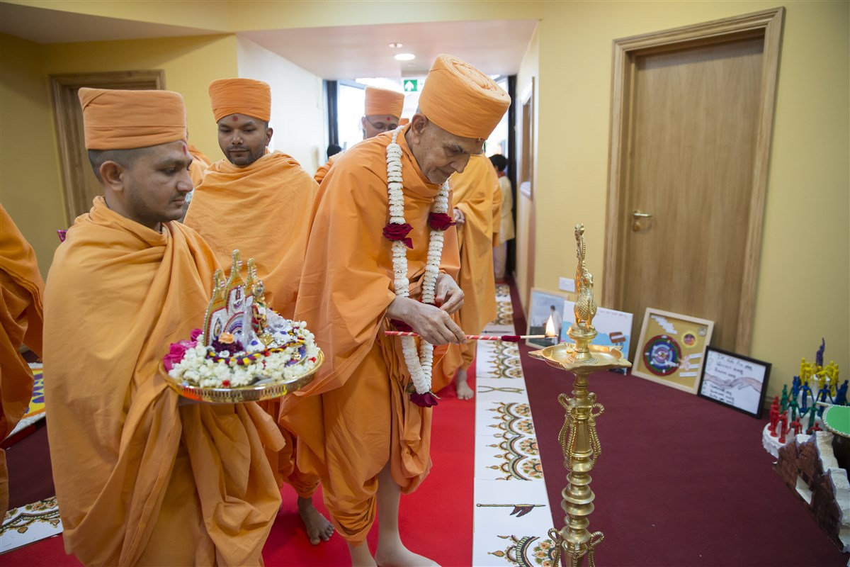 Swamishri lights a divo, marking the auspicious opening of the building