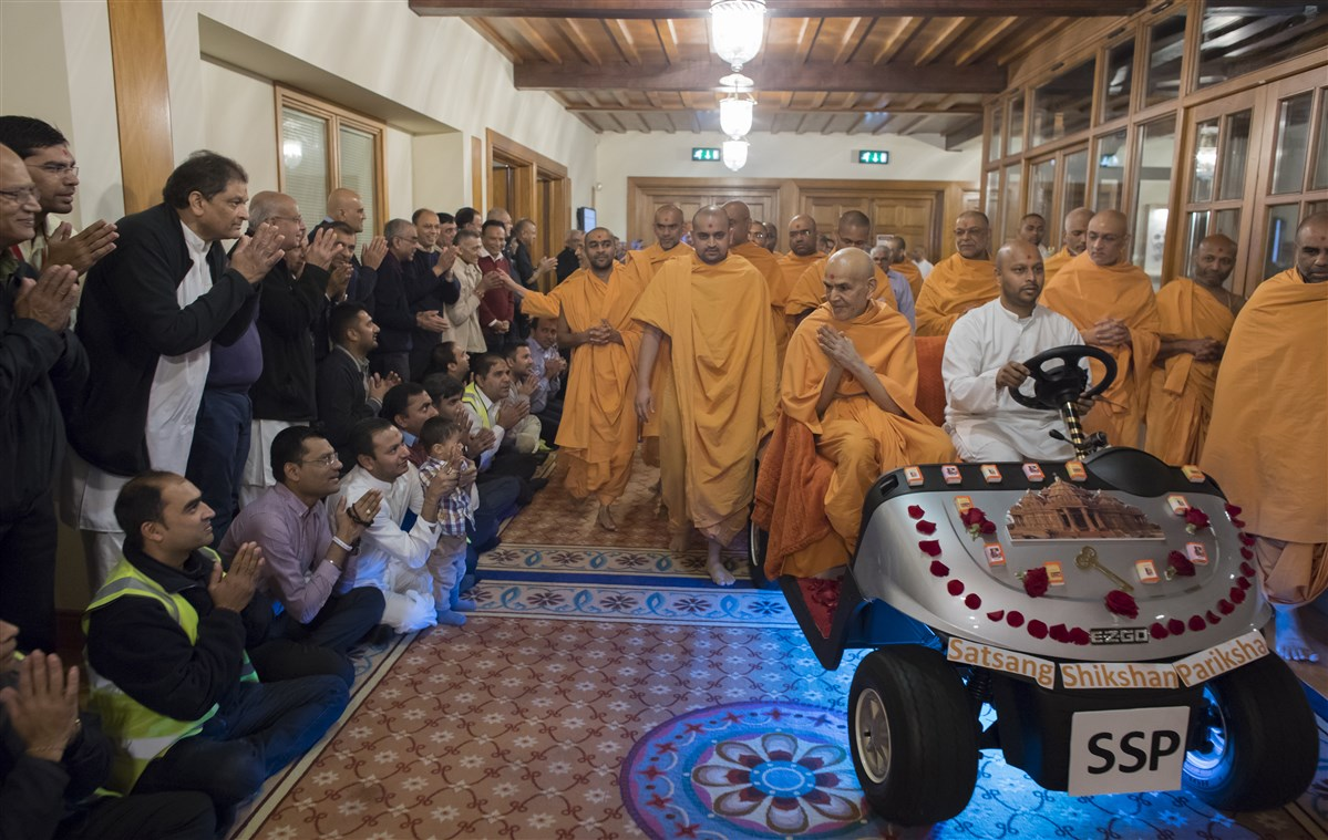 Swamishri greets devotees on his way to the assembly hall
