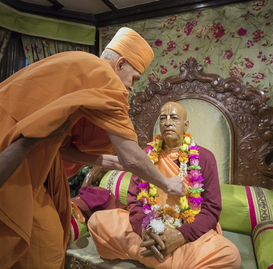 Swamishri offers a garland to the murti of Bhaktivedanta Swami Prabhupada