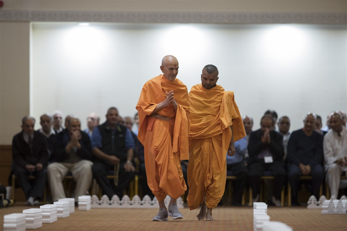 Swamishri folding his hands during his walk