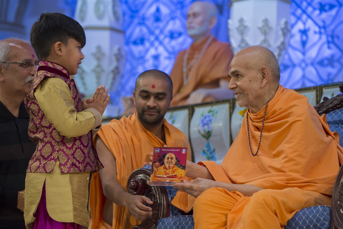 Swamishri blesses a child from Paris, accepting his invitation to grace Europe