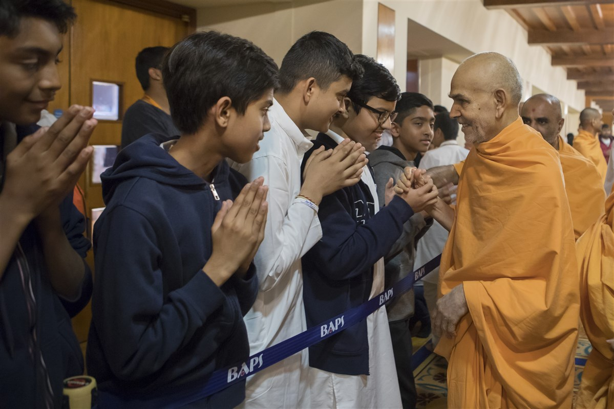Swamishri blesses children on his way from the assembly hall