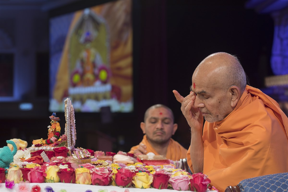 Swamishri offers his respects to the murtis in his puja