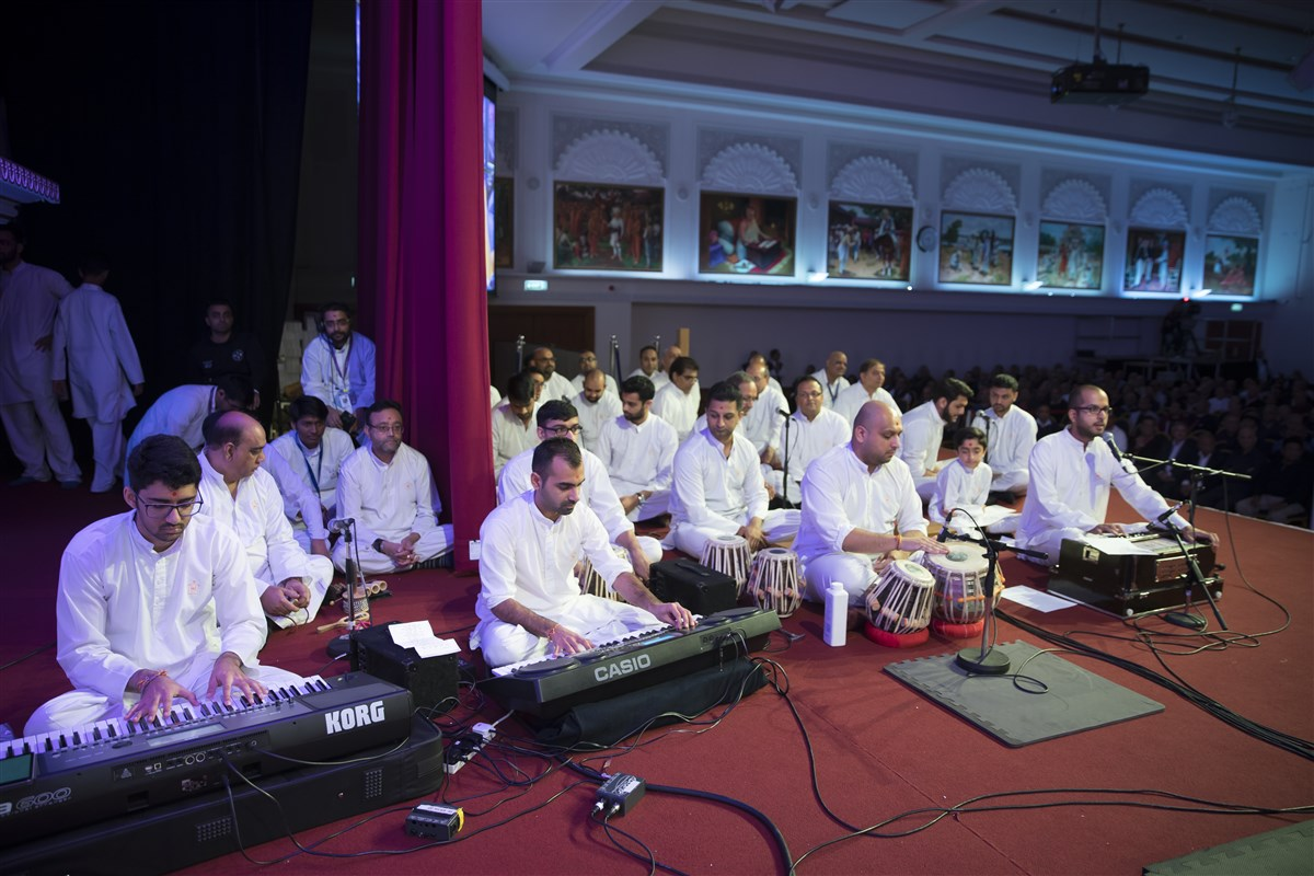 Devotees from around the UK collectively sing and perform in Swamishri's puja