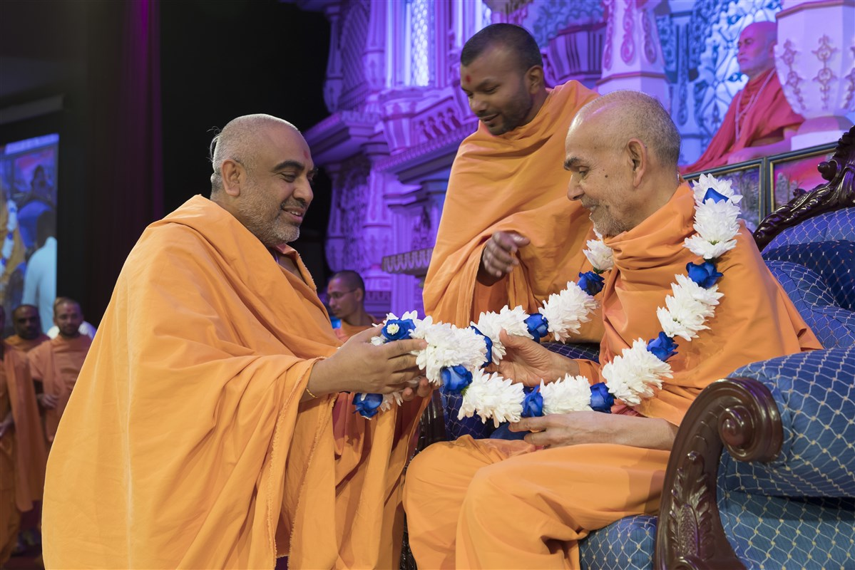 Yogvivekdas Swami honours Swamishri with a fresh flower garland