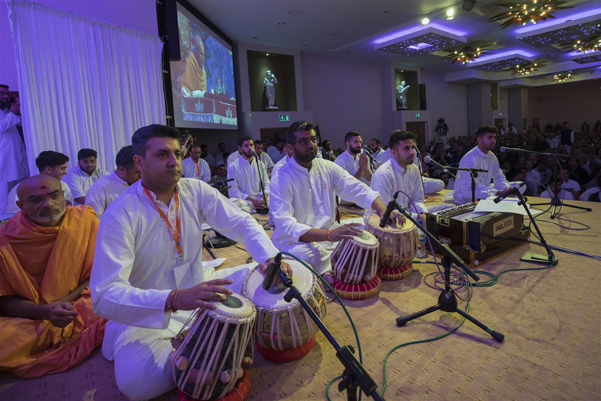 Devotees from around the UK sing and perform in Swamishri's puja