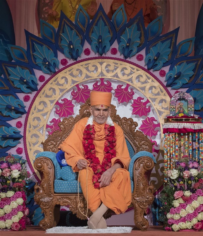 Swamishri is adorned with a pagh, chandan archa and a garland of fresh roses