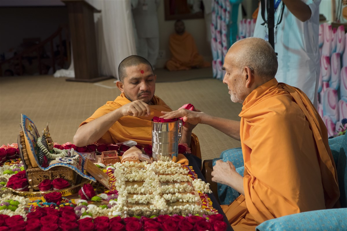 Swamishri sanctifies water with roses offered to the murtis in his puja