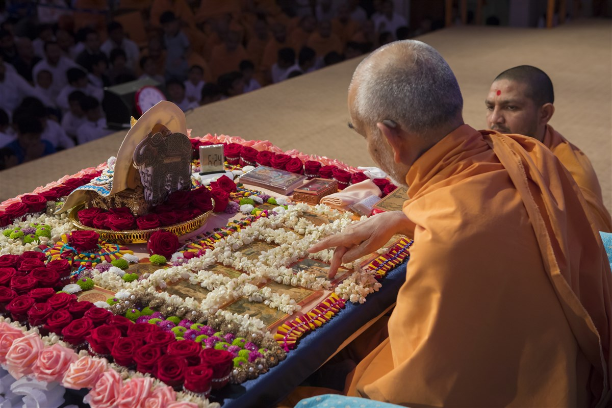 Swamishri reverently touches the murti of Pramukh Swami Maharaj in his puja