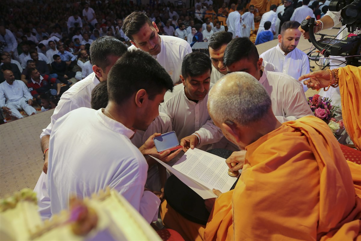 Swamishri provides his stamp of approval to the written account of yesterday's 'Vachanamrut Leicester 1'