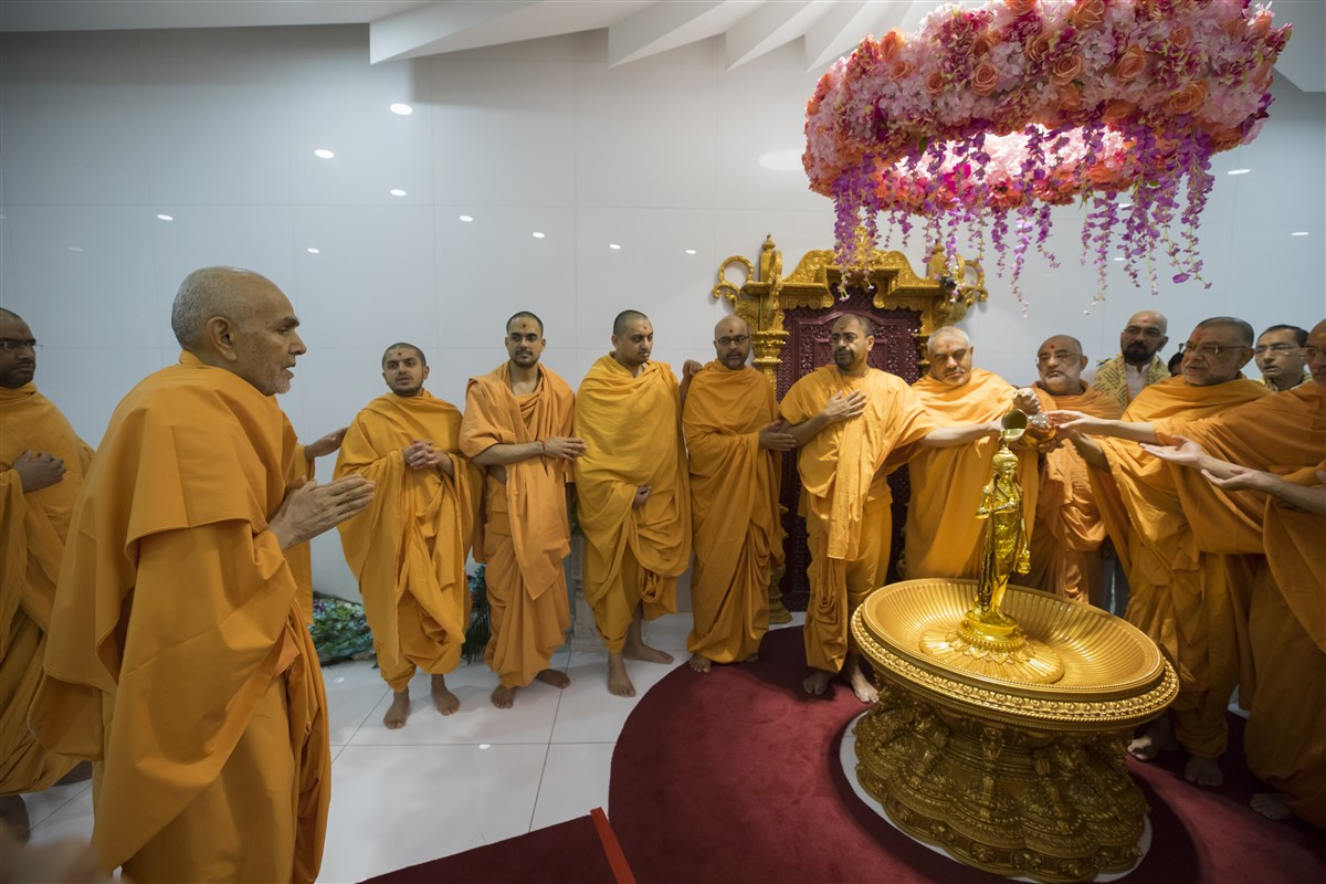 Swamishri engaged in darshan as swamis collectively offer an abhishek to Shri Nilkanth Varni