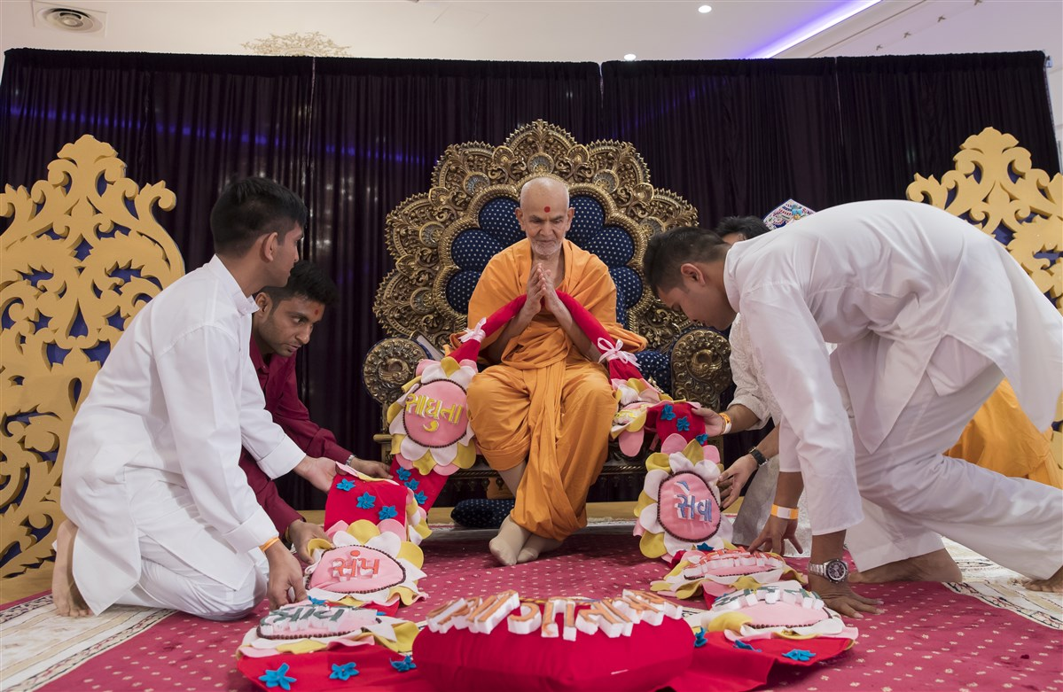Volunteers from Poland honour Swamishri with a decorative garland